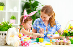 Happy family mother and child girl paints eggs for Easter Royalty Free Stock Photo