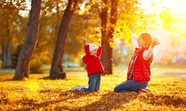 Happy family mother and child girl playing and throw leaves in a Royalty Free Stock Images