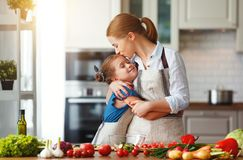 Happy family mother with child girl preparing vegetable salad. Happy family mother with child girl   preparing vegetable salad at home royalty free stock images