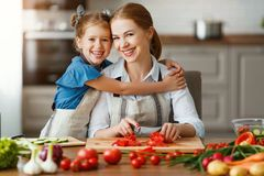 Happy family mother with child girl preparing vegetable salad. Happy family mother with child girl   preparing vegetable salad at home stock images