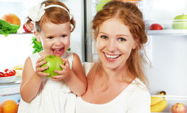 Happy family mother and child with healthy food fruits and vegetables. Happy family mother and child baby daughter around the refrigerator with healthy food royalty free stock photography