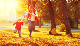 Happy family mother and child little daughter on autumn walk. Happy family mother and child little daughter running and playing on autumn walk Royalty Free Stock Photo