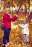 Happy family mother and child little daughter on autumn walk. Happy family mother and child little daughter running and playing on autumn walk Stock Images