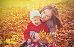 Happy family: mother and child little daughter play cuddling on autumn. Walk in nature outdoors Stock Photos