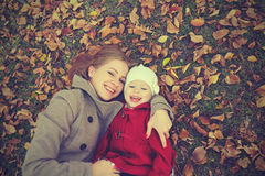 Happy family: mother and child little daughter play cuddling on autumn. Walk in nature outdoors Stock Photography