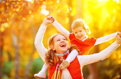 Happy family: mother and child little daughter play cuddling on. Autumn walk in nature outdoors Royalty Free Stock Image