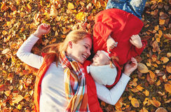 Happy family: mother and child little daughter play cuddling on. Autumn walk in nature outdoors stock image