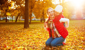 Happy family: mother and child little daughter play cuddling on. Autumn walk in nature outdoors Stock Photo