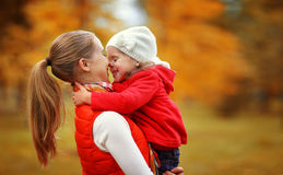 Happy family. mother and child little daughter play kissing on a. Utumn walk in nature outdoors Royalty Free Stock Photo