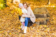 Happy family: mother and child little daughter play, laughing cuddling on autumn walk in nature outdoors Stock Photos