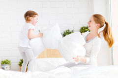 Happy family mother and child playing on bed and pillow fight Royalty Free Stock Image