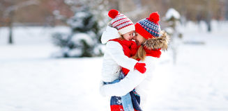 Happy family mother and child playing on winter walk. Happy family mother and child daughter playing and hugging  on a winter walk Royalty Free Stock Images