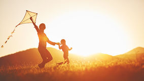 Happy family mother and child run on meadow with a kite in the s. Ummer on the nature royalty free stock photo