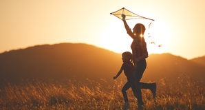 Happy family mother and child run on meadow with a kite in summe Stock Image