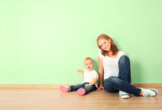 Happy family of mother and child sitting on the floor in an empt. Happy family of mother and child is a toddler sitting on the floor in an empty home wall in the Royalty Free Stock Photo