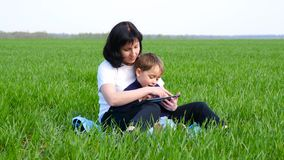 Happy family: mother and child sitting on the green grass. A mother and a little boy use a tablet to relax. Technology stock video