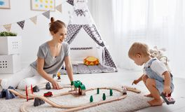 Happy family mother and child son playing in toy railway in pl. Happy family mother and child son playing together in toy railway in playroom royalty free stock photo