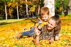 Happy family: mother and child sonr have fun in autumn on autumn. Park. Young Mother and kid girl hugging in leaves at fall. Beautiful picture in nature royalty free stock photo