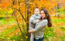 Happy family: mother and child sonr have fun in autumn on autumn park. Young Mother and kid girl hugging in leaves at fall. Beautiful picture in nature stock photography