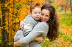 Happy family: mother and child sonr have fun in autumn on autumn park. Young Mother and kid girl hugging in leaves at fall. Beautiful picture in nature royalty free stock photos