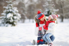 Happy family mother and child on winter walk drinking tea. Happy family mother and child daughter on a winter walk outdoors drinking tea stock photography