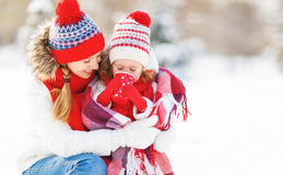 Happy family mother and child on winter walk drinking tea. Happy family mother and child daughter on a winter walk outdoors drinking tea royalty free stock photos