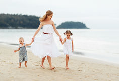 Happy family mother and children on beach by sea in summer Stock Images