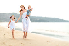 Happy family mother and children on beach by sea in summer Stock Photo