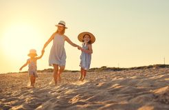 Happy family mother and children on beach by sea in summer. Happy family mother and children on the beach by the sea in summer royalty free stock photo