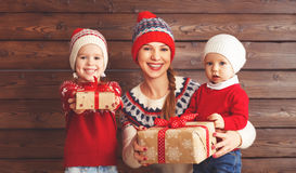 Happy family mother and children with christmas gift at wooden b. Happy family mother and children girl and boy  with christmas gift  at wooden background Royalty Free Stock Image