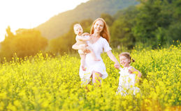 happy family, mother and children little daughter and baby running on meadow with yellow flowers stock image