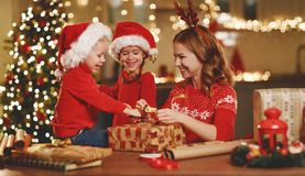 Happy family mother and children pack Christmas gifts stock images