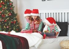 Happy family mother and children in pajamas opening gifts on chr royalty free stock image