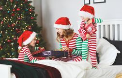 Happy family mother and children in pajamas opening gifts on chr royalty free stock photos