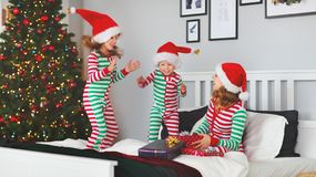 happy family mother and children in pajamas opening gifts on christmas morning near tree royalty free stock photography