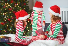 Happy family mother and children in pajamas opening gifts on christmas morning near christmas tree royalty free stock photography