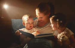 Happy family mother and children read a book in bed. Evening Stock Photography