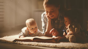 Happy family mother and children read a book in evening Royalty Free Stock Images
