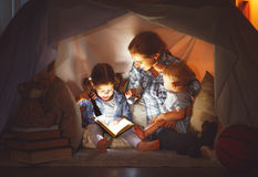 Happy family mother and children reading a book  in  tent at hom. Happy family mother and children reading a book with a flashlight in a tent at home Stock Images