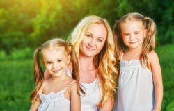 Happy family mother and children twin sisters on meadow in summe Royalty Free Stock Images