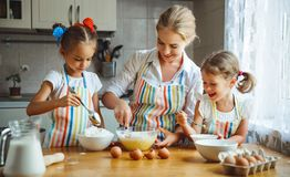 Happy family mother and children twins   bake kneading dough in. Happy family mother and children twins daughter bake kneading dough in the kitchen Royalty Free Stock Images