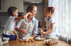 Happy family mother and children twins   bake kneading dough in Stock Images