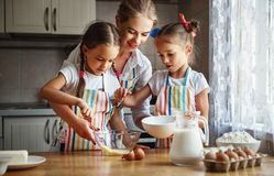 Happy family mother and children twins bake kneading dough in. Happy family mother and children twins daughter bake kneading dough in the kitchen royalty free stock image