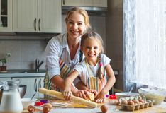 Happy family mother and daughter bake kneading dough in kitchen. Happy family mother and child daughter bake kneading dough in the kitchen Stock Photo