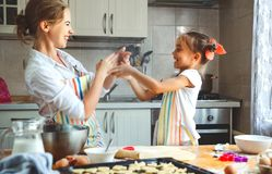 Happy family mother and daughter bake kneading dough in kitchen. Happy family mother and child daughter bake kneading dough in the kitchen stock images