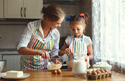 Happy family mother and daughter bake kneading dough in kitchen. Happy family mother and child daughter bake kneading dough in the kitchen Stock Photos