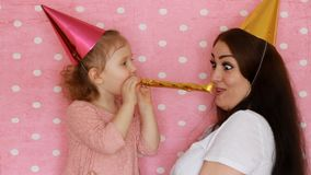 Happy family - Mother and daughter blowing party horns, smiles, hugs, laugh and celebrate birthday. A woman and her