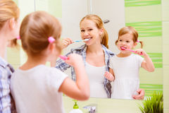 Happy family mother and daughter child brushing her teeth toothb. Happy family mother and daughter child girl brushing her teeth toothbrushes front of the mirror Royalty Free Stock Photo