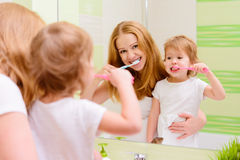 Happy family mother and daughter child brushing her teeth toothb Stock Photos