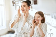 Mother and daughter caring for skin stock images